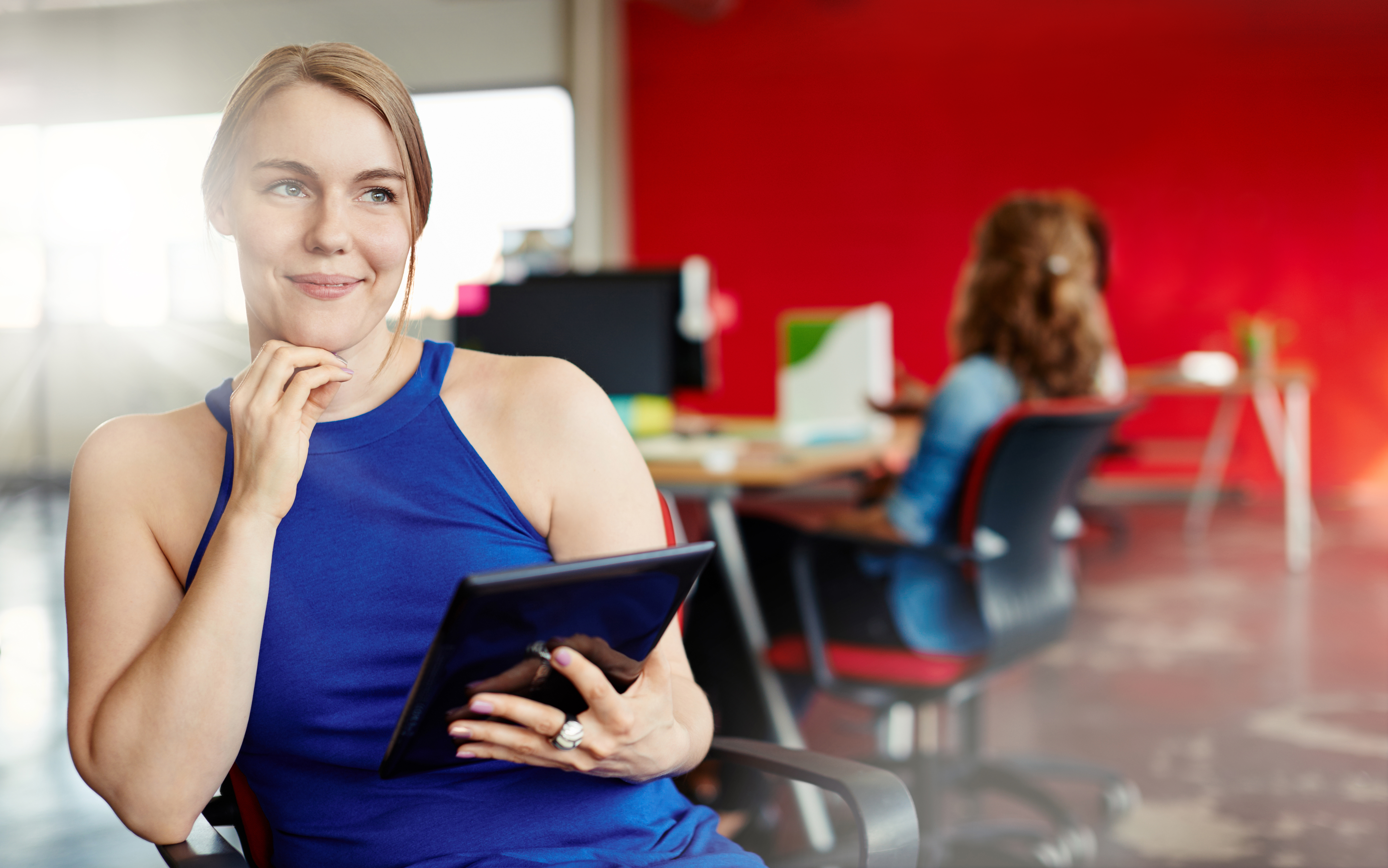 Woman sat in red office using a tablet with Reclaro on it