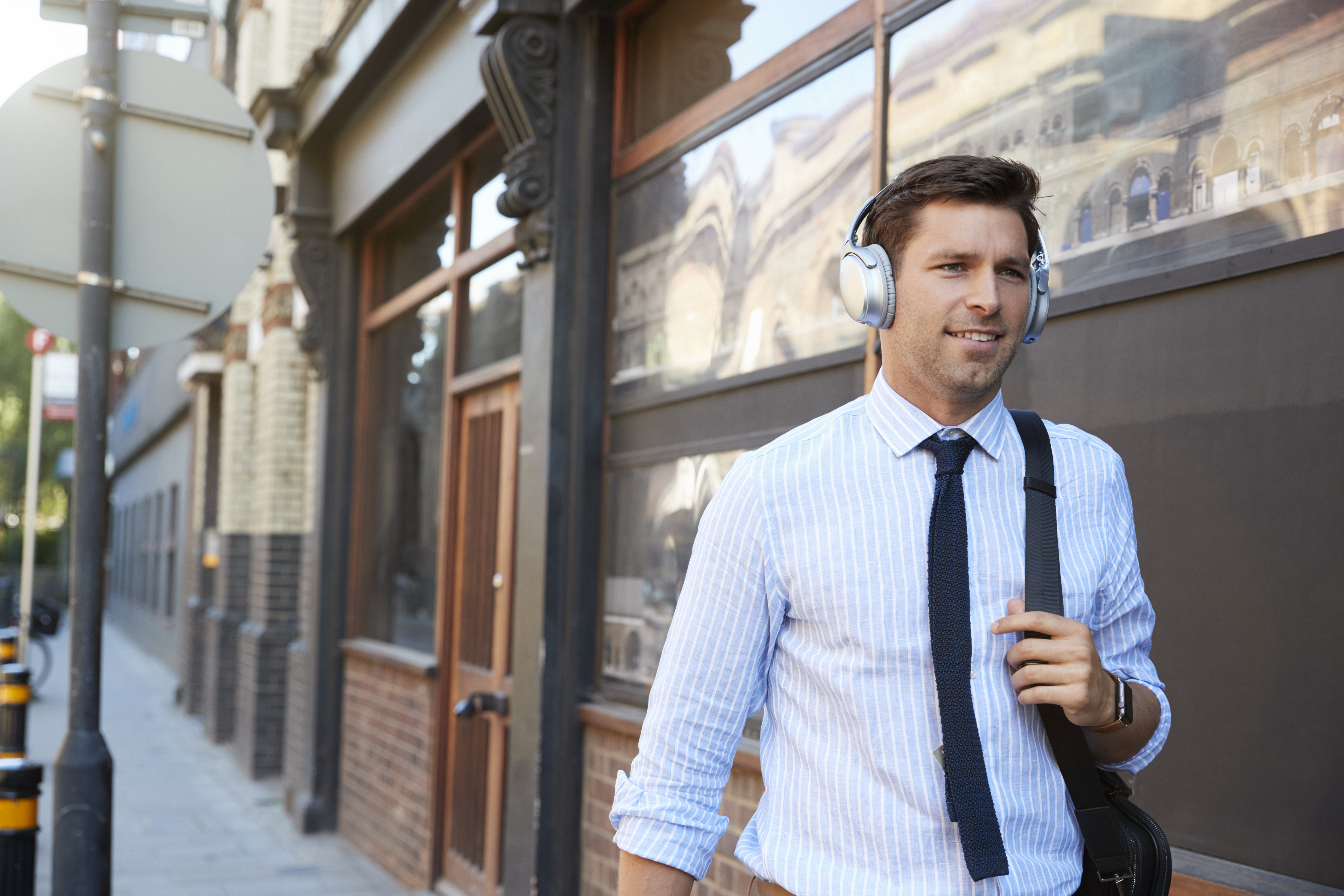Businessman smartly dressed walking down street wearing headphones and learning