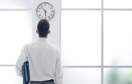 smartly dressed businessman holding folders whilst looking up at a clock