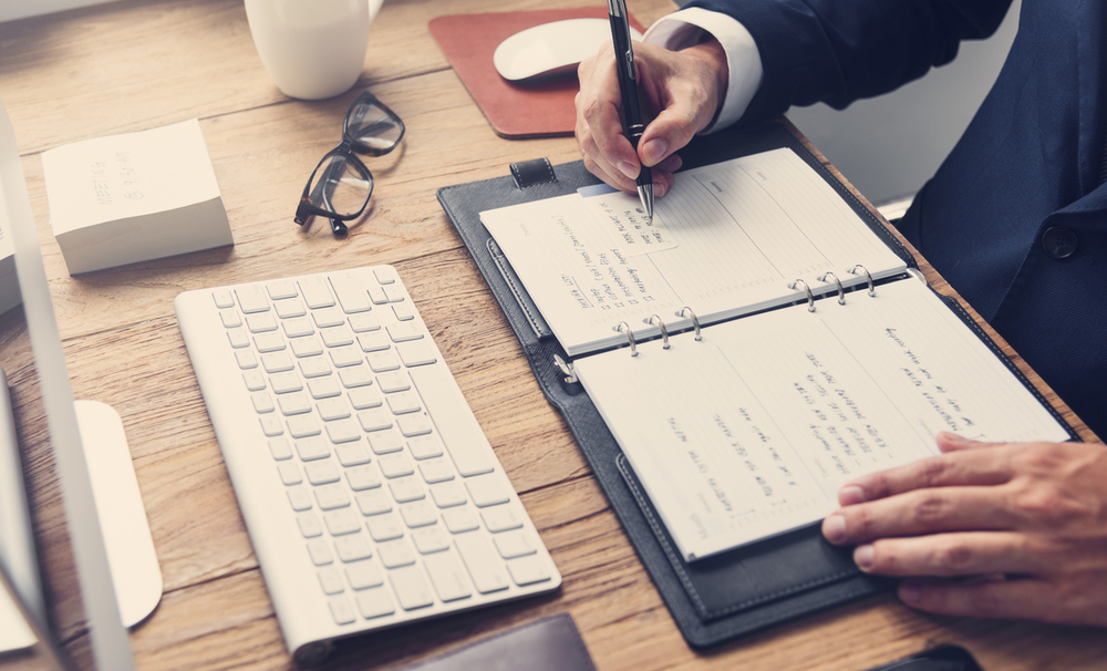 Business man writing with pen in notepad at desk